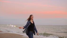 Jeune femme attirante se tenant prêt la mer pendant le coucher du soleil et tenant la bougie de scintillement brûlante Tir au ral banque de vidéos