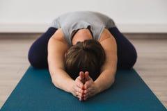 Jeune femme attirante sur le tapis de yoga faisant la pose du ` s d'enfant avec des paumes ensemble dans le namaste images stock