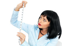 Jeune femme attirante tenant et regardant un ruban métrique Photographie stock libre de droits