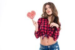 Jeune femme attirante tenant la lucette en forme de coeur Photo libre de droits