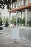 Jeune femme attirante tenant la toile vide à la rue et regardant de côté Photo libre de droits