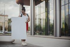 Jeune femme attirante tenant la toile vide et la regardant la rue Photographie stock