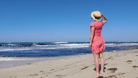 Jeune femme attirante tenant son chapeau et portant la robe rouge regardant la mer et l'horizon orageux La robe rouge s'agite sur banque de vidéos