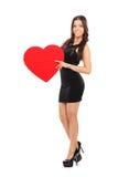 Jeune femme attirante tenant un coeur rouge Photos stock