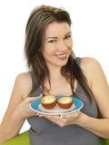 Jeune femme attirante tenant un plat des oeufs écossais photos libres de droits