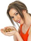 Jeune femme attirante tenant une poignée d'écrous mélangés Photos stock