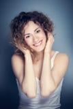Jeune femme attirante touchant ses cheveux et visage Photographie stock