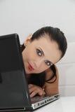 Jeune femme attirante travaillant sur son ordinateur portable à la maison Photos stock