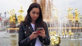 Jeune femme attirante utilisant la veste noire et à l'aide du téléphone intelligent moderne 4K clips vidéos