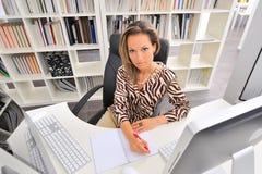 Jeune femme au bureau photos stock