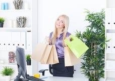 Jeune femme au bureau avec de beaux sacs Photo stock