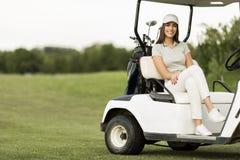 Jeune femme au chariot de golf photo stock