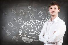 Jeune femme au-dessus de croquis de cerveau sur le mur en béton Image libre de droits