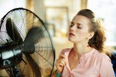 Jeune femme au foyer appr?ciant la fra?cheur devant la fan fonctionnante photographie stock libre de droits