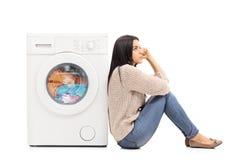 Jeune femme au foyer attendant la blanchisserie Photos stock