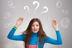 Jeune femme au foyer confuse avec les légumes tirés Photo stock