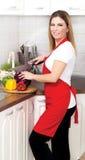 Jeune femme au foyer de sourire préparant un montant éligible maximum de végétarien Images stock