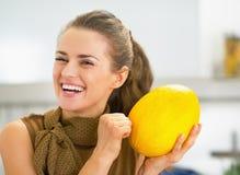 Jeune femme au foyer de sourire vérifiant la maturité du melon photo libre de droits