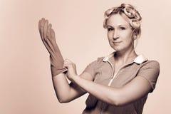 Jeune femme au foyer drôle avec des gants Images libres de droits