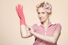 Jeune femme au foyer drôle avec des gants Photographie stock