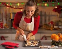 Jeune femme au foyer heureuse décorant des biscuits de Noël dans la cuisine Photos libres de droits