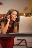 Jeune femme au foyer heureuse dans la robe rouge ayant la causerie visuelle sur l'ordinateur portable Images stock