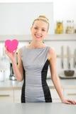 Jeune femme au foyer heureuse montrant le coeur dans la cuisine Image libre de droits