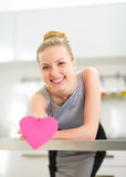 Jeune femme au foyer heureuse montrant le coeur dans la cuisine Photo stock