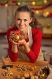 Jeune femme au foyer heureuse montrant le pot avec des écrous de miel Photographie stock libre de droits