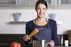 Jeune femme au foyer préparant des pâtes italiennes saines Image stock