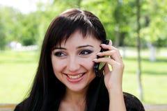 Jeune femme au parc de ressort parlant au téléphone. Photographie stock