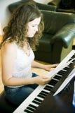 Jeune femme au piano photo stock