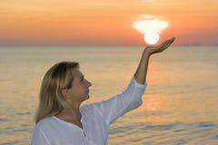 Jeune femme au temps de lever de soleil Photos stock