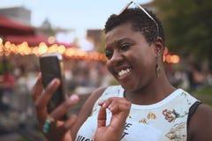 Jeune femme authentique d'afro-américain à l'aide d'un téléphone portable à un festival de musique d'été Image libre de droits
