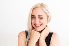 Jeune femme aux cheveux blonds donnant le clin d'oeil à l'appareil-photo images libres de droits