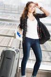 jeune femme aux cheveux foncés se tenant avec une valise et un sac à dos et tenant un passeport avec un billet D'isolement sur le Photos stock