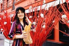 Jeune femme aux cheveux longs de brune dans une robe lumineuse contre un mur rouge photographie stock
