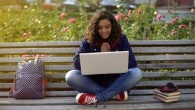Jeune femme aux cheveux ondulés communiquant avec des amis au-dessus d'appareil-photo d'ordinateur portable dehors Photographie stock libre de droits