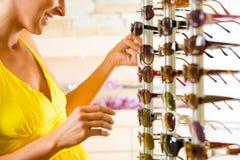 Jeune femme aux lunettes de soleil d'achats d'opticien Photographie stock