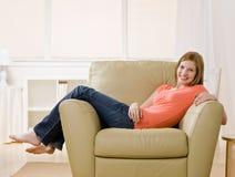Jeune femme aux pieds nus lounging sur le fauteuil à la maison Image libre de droits