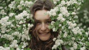Jeune femme aux yeux verts de sourire heureuse avec des fleurs regardant l'appareil-photo Beauté normale clips vidéos
