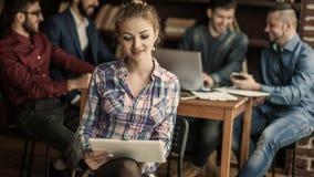 Jeune femme auxiliaire avec l'ordinateur portable sur le fond des affaires Image libre de droits