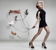 Jeune femme avec beaucoup de chaussures Photo stock