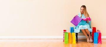 Jeune femme avec beaucoup de paniers brillamment colorés images stock