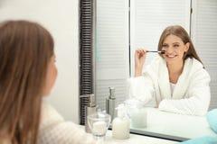 Jeune femme avec de longs cils et brosse près de miroir image libre de droits