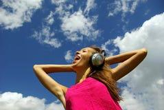 Jeune femme avec des écouteurs à l'extérieur image libre de droits