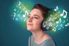 Jeune femme avec des écouteurs écoutant la musique Photo stock