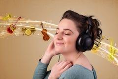 Jeune femme avec des écouteurs écoutant la musique Photographie stock