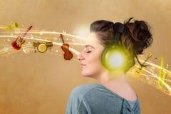 Jeune femme avec des écouteurs écoutant la musique Images libres de droits