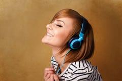 Jeune femme avec des écouteurs écoutant la musique avec l'espace de copie Photographie stock libre de droits